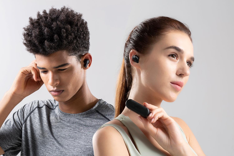 1MORE PistonBuds, en man och en kvinna med varsin uppsättning hörlurar i öronen.